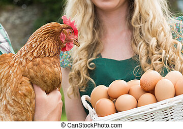 Young couple holding chicken and basket of eggs in the...