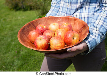 Woman holding a bowl of fresh red apples
