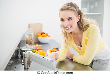 Happy cute blonde using tablet in bright kitchen
