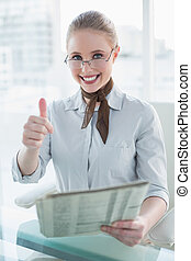 Blonde cheerful businesswoman holding newspaper and showing...
