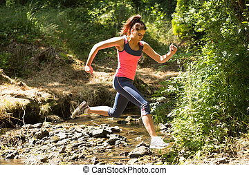 Sporty young woman leaping over a stream in a forest on a...