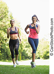 Two fit brunette women jogging towards camera in a forest