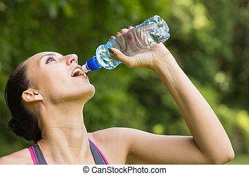 Fit woman drinking water from sports bottle outside on sunny...