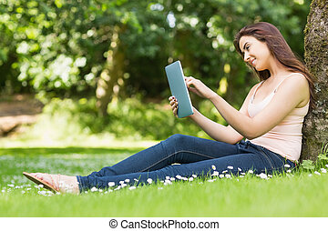 Happy woman leaning against a tree working with her tablet...