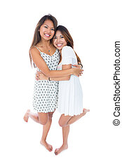 Two cheerful asian sisters embracing each other