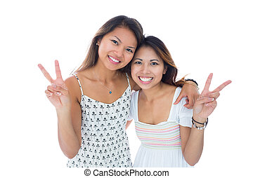 Two smiling young women making a peace gesture on white...