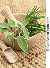 mortar and pestle with herbs and spices on a jute background