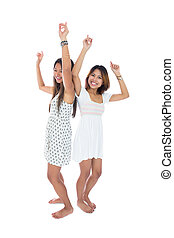 Two beautiful young women dancing on white background