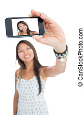 Smiling asian woman taking a selfie using her smartphone
