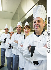 Team of happy chefs smiling at the camera in a kitchen...