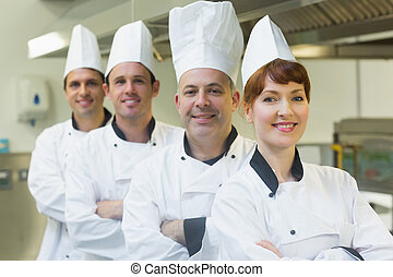 Group of happy chefs smiling at the camera in a kitchen...