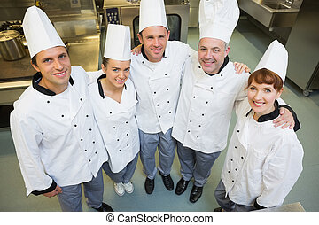 Five happy chefs smiling up at the camera in a kitchen...