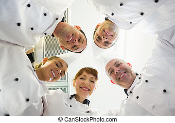 Five smiling chefs standing in a circle looking down at...