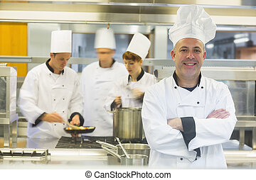 Mature male chef posing with crossed arms while colleagues...