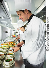 Smiling handsome chef seasoning his soup standing in the...
