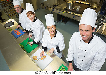 Four chefs preparing food at count