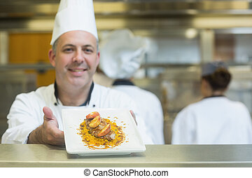 Experienced mature chef presenting a dish smiling at the...