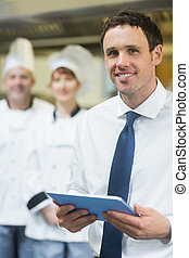 Young restaurant manager holding his tablet smiling at the...