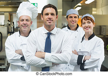 Restaurant manager standing in front of team of chefs...
