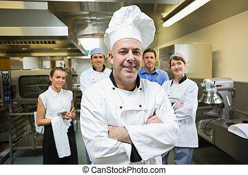 Head chef posing with team behind him in a professional...