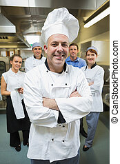 Head chef posing with his team behind him in restaurant...