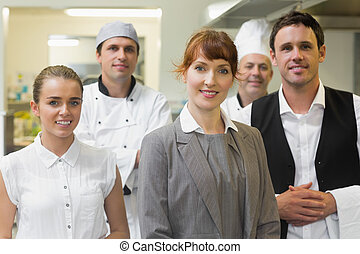 Young female manager posing in a modern kitchen with the...