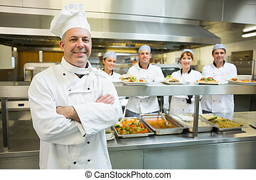 Proud mature head chef posing in a modern kitchen with his...