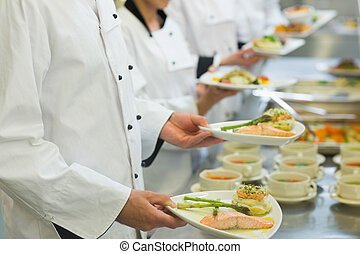 Chef holding salmon dishes standing in a row with colleagues
