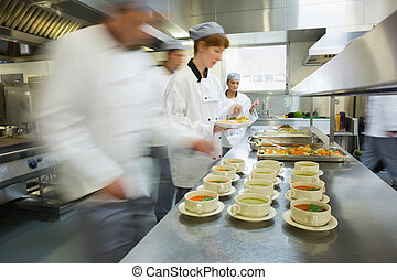 Four chefs working in a modern kitchen preparing soups