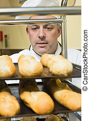 Head chef pushing a trolley with baguettes on it