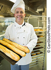 Mature baker presenting proudly some baguettes on a baking...