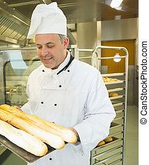 Mature head chef holding some baguettes