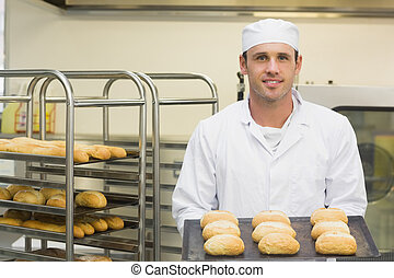 Happy young baker holding some rol