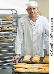 Young male baker standing in a kitchen in front of baguettes...
