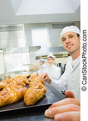 Young male baker standing in a bak