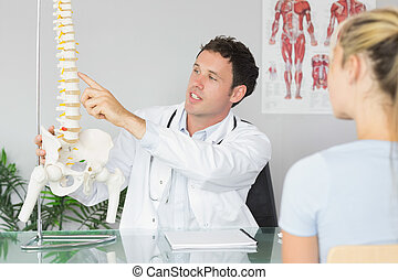 Handsome doctor showing a patient something on skeleton...