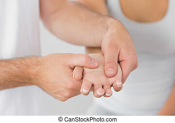 Physiotherapist massaging patients hand