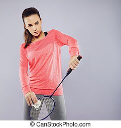 Young woman with badminton racket ready to serve