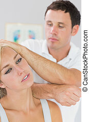 Calm physiotherapist massaging patients neck with elbow in...