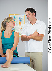 Attractive physiotherapist and patient looking at each other...