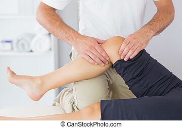 Physiotherapist controlling knee of a patient in bright...