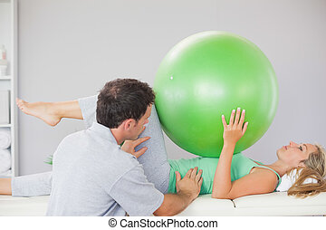 Patient holding exercise ball over chest in bright office