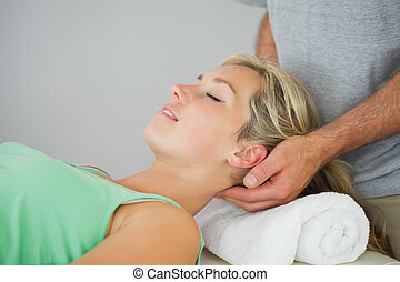 Physiotherapist massaging patients head in bright office