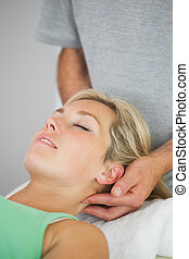 Physiotherapist holding patients head in bright office