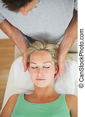 Physiotherapist massaging the head of a patient