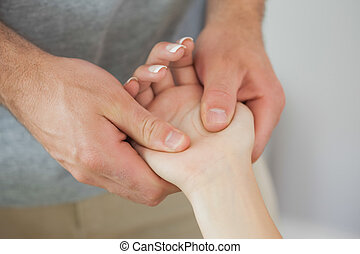 Physiotherapist checking the hand of a patient