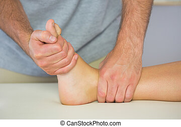 Physiotherapist examining patients foot in bright office
