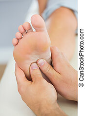 Picture of foot massage given from physiotherapist in bright...