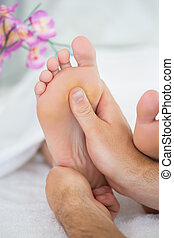 Close up of physiotherapist giving a patient a foot massage...