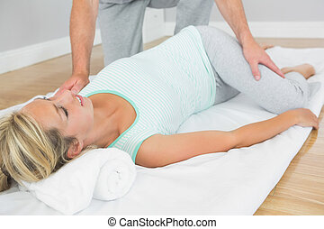 Physiotherapist checking patients hips on a mat on the floor...